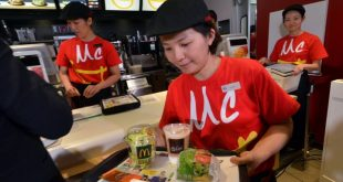 "An employee of McDonald's Japan serves the new menu ""Vegetable Chicken Burger"" as the company president Sarah Casanova announces the new business strategy at a restaurant in Tokyo on May 21, 2015. McDonald's Japan unveiled a revamped business strategy and a new menu on May 21 as it looks to put a damaging contamination scandal behind it. AFP PHOTO / Yoshikazu TSUNO        (Photo credit should read YOSHIKAZU TSUNO/AFP/Getty Images)"